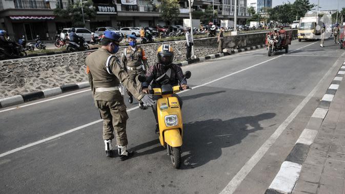 Petugas gabungan memberhentikan pengendara motor yang tidak mengenakan masker di kawasan Sunter, Jakarta, (3/9/2020). Dari total sanksi denda PSBB transisi di Jakarta yang mencapai Rp4 Miliar, Rp2,1 Miliar diantaranya merupakan denda pelanggar tidak menggunakan masker. (merdeka.com/Iqbal Nugroho)