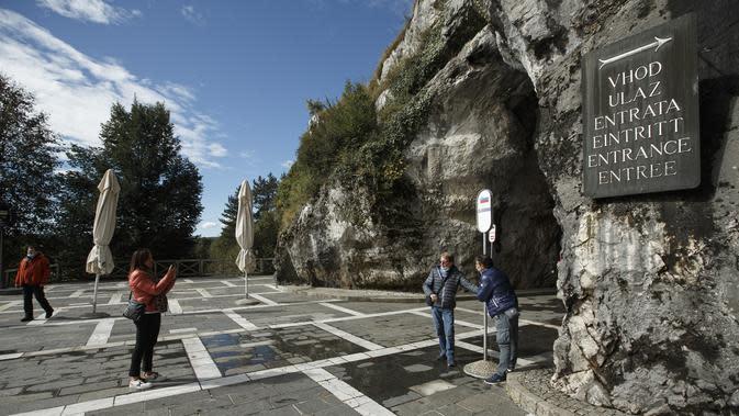 Sejumlah pengunjung berpose untuk difoto di depan pintu masuk Gua Postojna, Slovenia, 29 September 2020. Gua Postojna merupakan salah satu objek wisata alam terkenal di Slovenia. (Xinhua/Zeljko Stevanic)