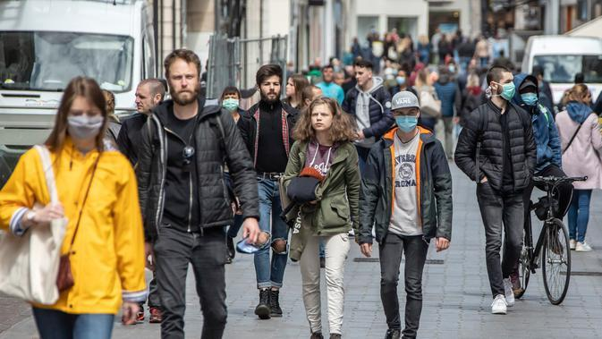 Orang-orang mengenakan masker berjalan di Lille, Prancis utara, (11/5/2020). Prancis mulai melonggarkan pembatasan pergerakan mulai Senin (11/5) melalui