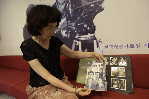 "Seong Ryeong-chul, a daughter-in-law of late South Korean director Min Kyoung-sik, shows leaflets and photos of Min's movie ""The Street of the Sun,"" before its first screening in six decades at Korean Film Archive in Seoul, South Korea, Tuesday, June 25, 2013. The only surviving Korean War-era South Korean film by director Min, got the screening Tuesday, the 63rd anniversary of the beginning of the war. Now digitally restored, it offers South Koreans a rare glimpse at how their ancestors lived amid the destruction and poverty of war. The movie was the debut feature of Min, a South Korean director who took a camera to the streets of Daegu in 1952, while a stream of refugees poured in. (AP Photo/Lee Jin-man)"