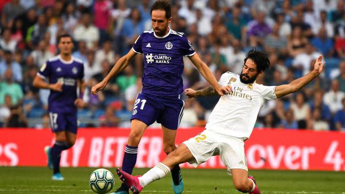 Gelandang Real Madrid, Isco, menekel gelandang Valladolid, Michel, pada laga La Liga di Stadion Santiago Bernabeu, Madrid, Sabtu (24/8). Kedua klub bermain imbang 1-1. (AFP/Gabriel Bouys)