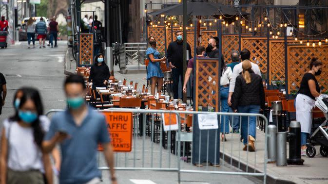 Para pejalan kaki yang memakai masker berjalan melewati tempat makan terbuka di Distrik Keuangan, New York, Amerika Serikat, 25 September 2020. Hingga 25 September 2020, sebanyak 7.005.746 orang di Amerika Serikat terinfeksi COVID-19, dengan 203.240 orang meninggal dunia. (Xinhua/Michael Nagle)