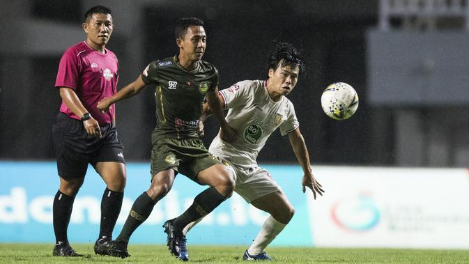 Gelandang Tira Persikabo, Roni Sugeng, berebut bola dengan gelandang Persela Lamongan. Kei Hirose, pada laga Liga 1 di Stadion Pakansari, Bogor, Senin (16/12). Kedua klub bermain imbang 1-1. (Bola.com/Vitalis Yogi Trisna)