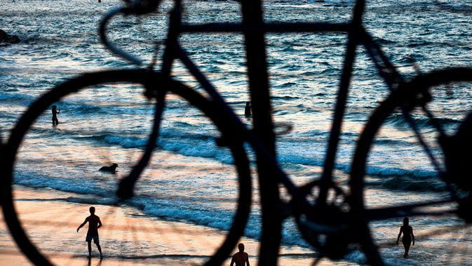 Orang-orang menjadi siluet oleh matahari terbenam di pantai yang hampir sepi selama penguncian nasional selama tiga minggu untuk mengekang penyebaran virus corona di pantai Laut Mediterania, Tel Aviv, Israel, Senin (21/9/2020). (AP Photo/Oded Balilty)