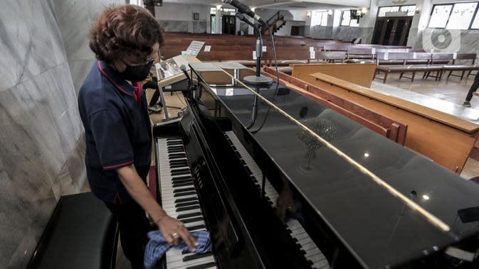 Karyawan membersihkan piano untuk menyambut kenormalan baru di Gereja Protestan Indonesia Bagian Barat (GPIB) Effatha, Jakarta, Sabtu (4/7/2020). GPIB Effatha menerapkan protokol kesehatan seiring kembali dibukanya gereja tersebut untuk ibadah di tengah pandemi COVID-19. (Liputan6.com/Johan Tallo)