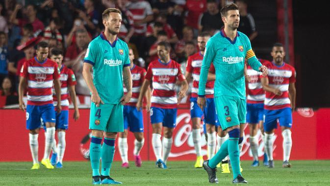 Reaksi gelandang Barcelona, Ivan Rakitic (kiri) dan rekannya, Gerard Pique setelah pemain Granada, Ramon Azeez mencetak gol pada laga pekan kelima La Liga di Stadion Nuevo Los Cármenes, Sabtu(21/9/2019). Barcelona tumbang dalam lawatannya ke markas tim promosi, Granada 0-2. (JORGE GUERRERO/AFP)
