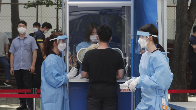Seorang pekerja medis membawa sampel dari petugas polisi selama pengujian COVID-19 di Badan Kepolisian Metropolitan Seoul di Seoul, Korea Selatan, Rabu, (19/8/2020). (AP Photo / Ahn Young-joon)