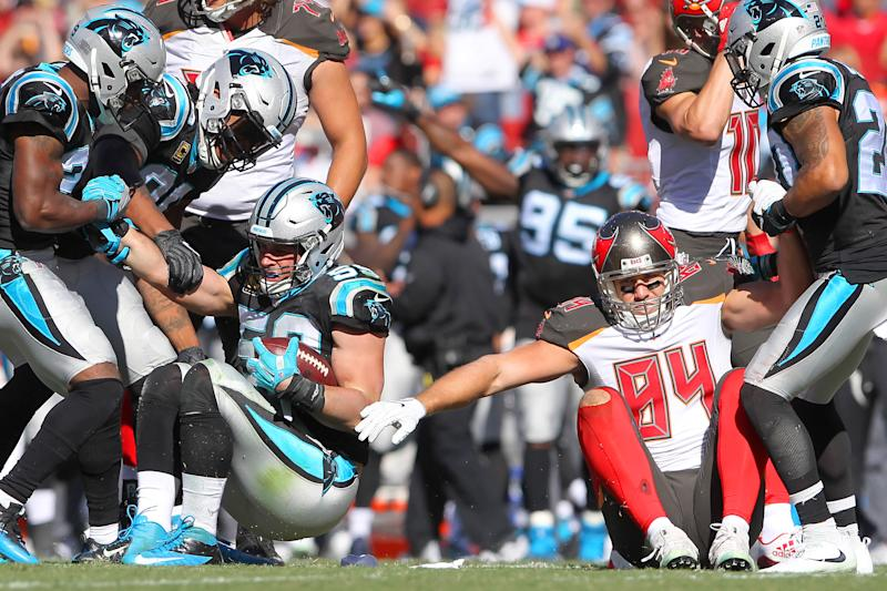 TAMPA, FL - OCTOBER 29: Luke Kuechly (59) of the Panthers is helped up after intercepting a Jameis Winston pass intended for Cameron Brate (84) of the Bucs during the regular season game between the Carolina Panthers and the Tampa Bay Buccaneers on October 29, 2017 at Raymond James Stadium in Tampa, Florida. (Photo by Cliff Welch/Icon Sportswire via Getty Images)