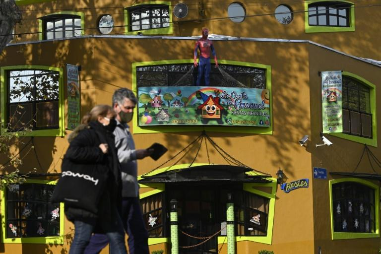 People walk by a closed children's party venue in Buenos Aires on June 9, 2020, during the government-imposed lockdown to prevent the spread of the coronavirus