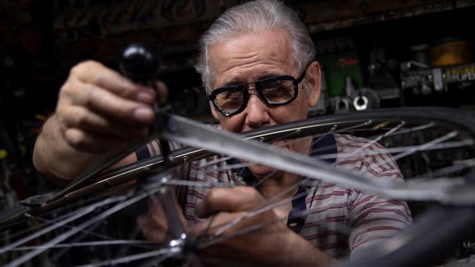 Raffaello Bianco, mekanik dan pecinta sepeda memperbaiki roda di bengkel mekaniknya di ruang bawah tanah apartemennya di Turin, Italia, 7 Juli 2020. Sepanjang hidupnya Bianco bekerja sebagai dokter hewan, tetapi ia mengatakan sepeda selalu memiliki gairah yang lebih besar. (MARCO BERTORELLO/AFP)
