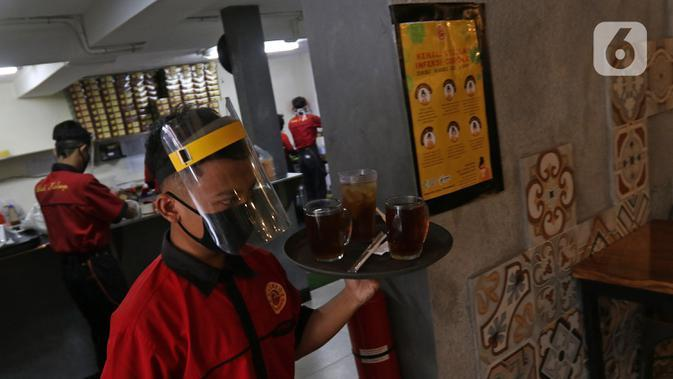 Pramusaji membawakan minuman pelanggan di restoran Bebek Kaleyo, Kemanggisan, Jakarta, Senin (12/10/2020). Pada penerapan kembali masa PSBB Transisi Jakarta, restoran dan cafe diperbolehkan melakukan pelayanan makan di tempat dengan protokol kesehatan yang ketat. (Liputan6.com/Herman Zakharia)