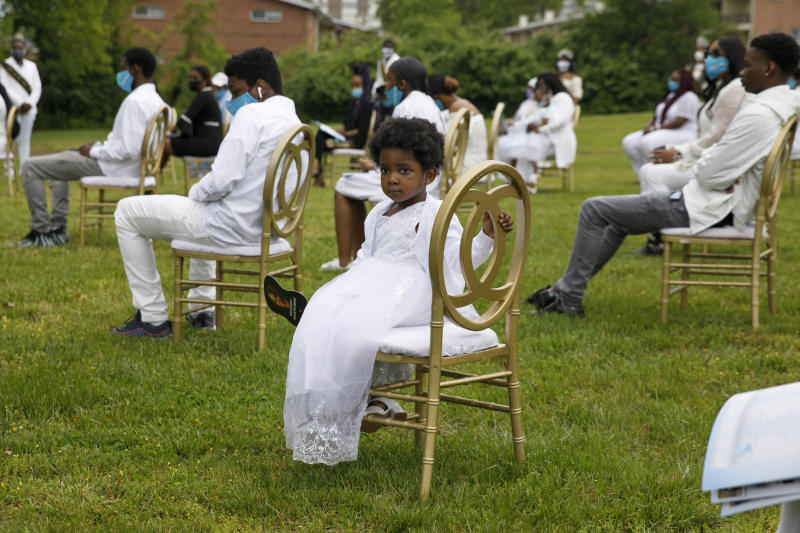 Amora, a grandchild of Joanne Paylor, 62, of southwest Washington, holds a fan with her grandmother's image on it during her outdoor memorial service at Cedar Hill Cemetery in Suitland-Silver Hill, Md., Sunday, May 3, 2020. Guests were seated in golden chairs six feet apart across the lawn to comply with social distancing rules. Despite not having died from coronavirus, almost every aspect of her funeral has been impacted by the pandemic. (AP Photo/Jacquelyn Martin)