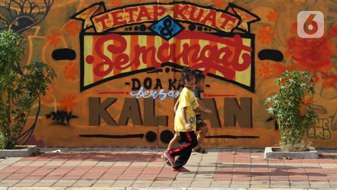 Anak-anak berjalan di depan mural bertema pandemi virus corona COVID-19 di kawasan Sunter, Jakarta, Selasa (2/6/2020). Mural tersebut dibuat sebagai wujud dukungan terhadap tenaga medis serta masyarakat agar tetap semangat menghadapi pandemi COVID-19. (Liputan6.com/Immanuel Antonius)