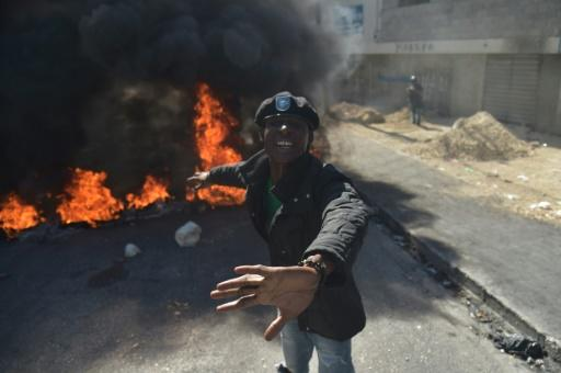 A demonstrator gestures in front of burning tires during protests in Port-au-Prince
