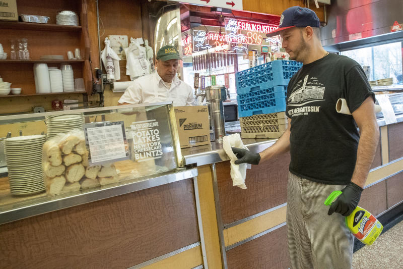 In this March 19, 2020 photo,  an employee disinfects the counter at Katz's Delicatessen on the Lower East Side of New York. The iconic eatery is only open for take out and delivery orders due to the coronavirus outbreak. (AP Photo/Mary Altaffer)