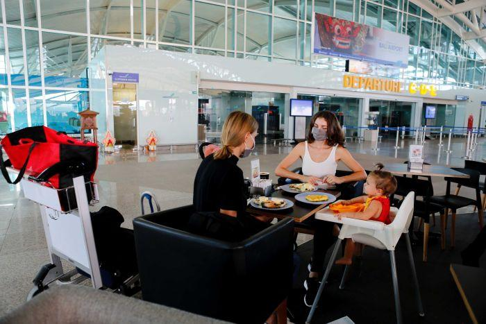 Two women and a baby wait for a flight as they sit at a cafe at a near-empty airport in Bali.