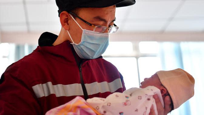 Hao Tiedan, seorang petugas medis, menggendong putrinya yang baru lahir di Taiyuan, Provinsi Shanxi, China utara, pada 4 Februari 2020, sebelum bertolak menuju Provinsi Hubei, China tengah, untuk bergabung dalam upaya memerangi coronavirus baru. (Xinhua/Cao Yang)