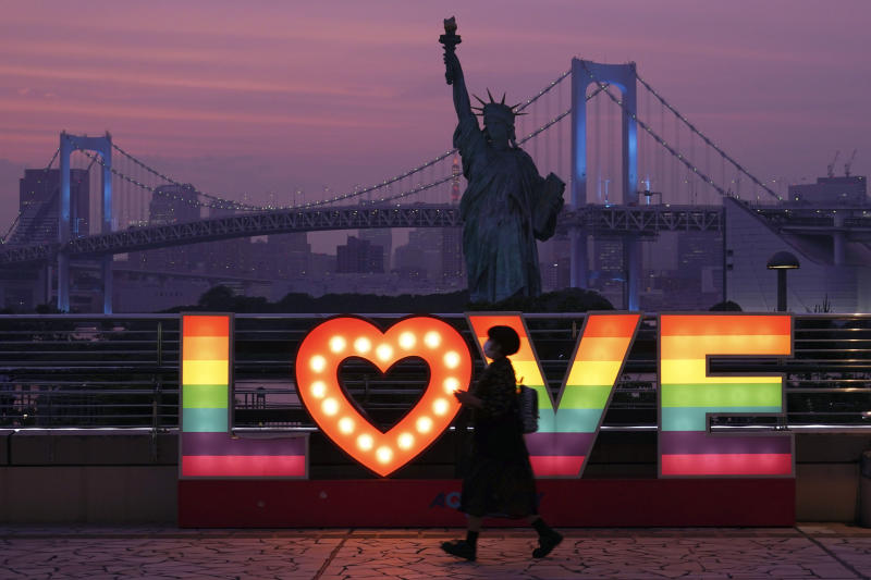 A visitor walks at Odaiba at sunset Wednesday, June 3, 2020, in Tokyo. A coronavirus state of emergency has been lifted, ending the restrictions nationwide as businesses began to reopen.(AP Photo/Eugene Hoshiko)