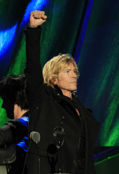 Guns N' Roses' Duff McKagan gestures after the band was inducted into the Rock and Roll Hall of Fame Saturday, April 14, 2012, in Cleveland. (AP Photo/Tony Dejak)