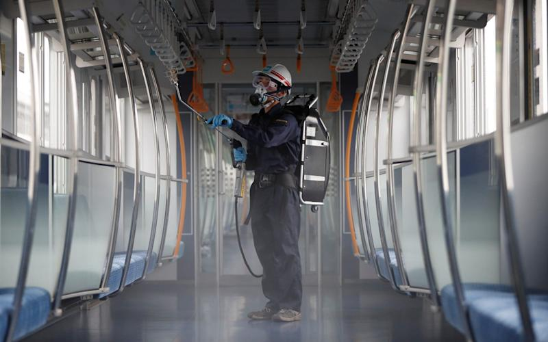 An employee of the Tokyo Metro sprays chemicals for anti-virus and bacteria coating to prevent infections - REUTERS/Issei Kato