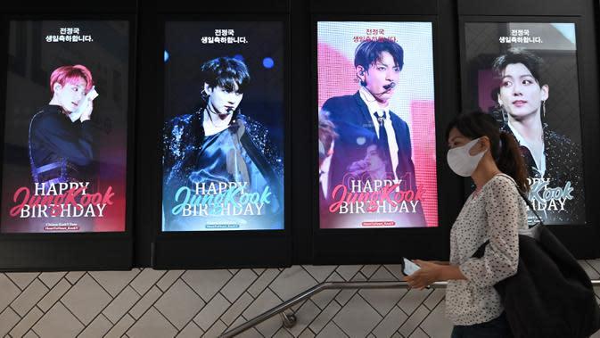 Seorang perempuan melewati layar listrik yang menunjukkan anggota boyband K-pop, BTS, di di stasiun kereta bawah tanah di Seoul, Selasa (1/9/2020). Bangtan Boys (BTS) menjadi artis Korea Selatan pertama yang berhasil menempati puncak Billboard Hot 100 dengan lagu Dynamite. (Jung Yeon-je/AFP)