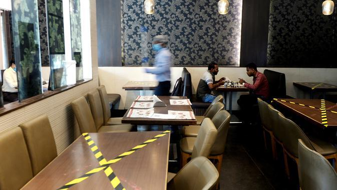 Orang-orang duduk dengan menjaga jarak di sebuah restoran yang dibuka kembali usai pelonggaran lockdown di Chennai, India, Senin (8/6/2020). Fase kelima karantina wilayah (lockdown) dimulai pada 1 Juni di India, dengan sejumlah pelonggaran untuk membuka kembali kegiatan ekonomi. (Arun SANKAR / AFP)