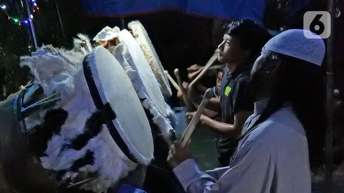 Sejumlah warga memukul bedug pada malam takbiran di kawasan Tanah Baru, Bogor, Jawa Barat, Sabtu (23/5/2020). Di tengah pandemi virus corona COVID-19, sejumlah warga tetap merayakan malam takbiran dengan memukul bedug. (Liputan6.com/Herman Zakharia)