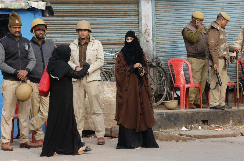 Muslim women cross a street lines with police personnel in Lucknow, in the northern Indian state of Uttar Pradesh, Friday, Dec. 27, 2019. Paramilitary and police forces were deployed and the internet shut down Friday in Muslim-majority districts in Uttar Pradesh, where more than a dozen people have been killed and more than 1,000 people arrested in protests that have erupted nationwide against a new citizenship law that excludes Muslims. (AP Photo/Rajesh Kumar Singh)