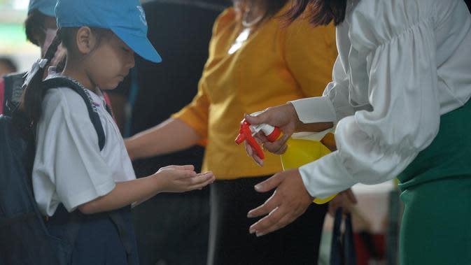 Seorang siswi membersihkan tangannya di pintu masuk sebuah sekolah di Bangkok, Thailand (1/7/2020). Sekolah-sekolah di Thailand telah dibuka kembali pada Rabu (1/7). (Xinhua/Rachen Sageamsak)