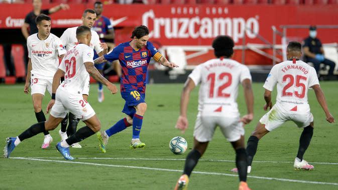 Striker Barcelona, Lionel Messi, berusaha melewati pemain Sevilla dalam laga lanjutan La Liga Spanyol, Sabtu (20/6/2020) dini hari WIB. Barcelona bermain imbang 0-0 atas Sevilla. (AFP/Cristina Quicler)