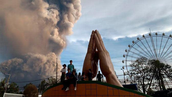 Sejumlah orang menyaksikan Gunung Api Taal erupsi di Tagaytay, Provinsi Cavite, Filipina, Minggu (12/1/2020). Ribuan orang yang tinggal di dekat gunung tersebut kemudian dievakuasi dari rumah mereka. (AP Photo/Bullit Marquez)