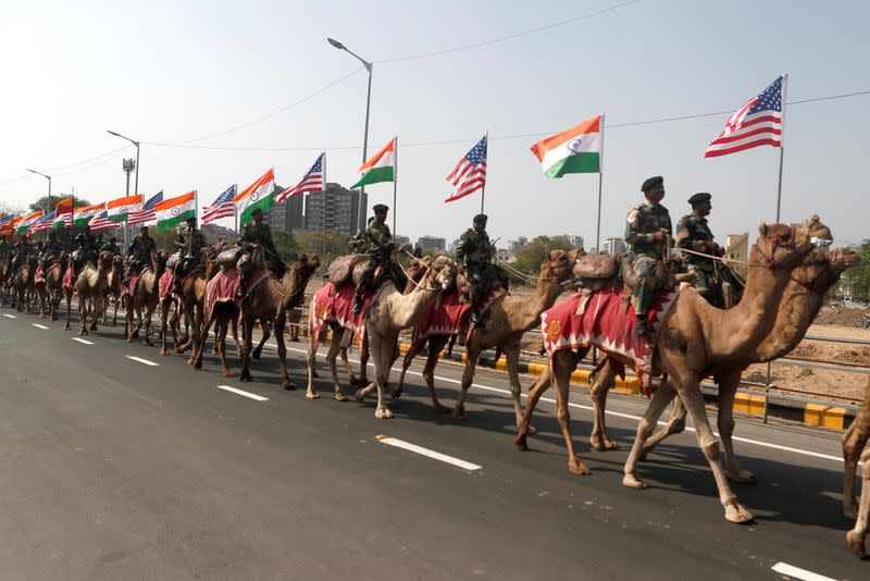 Border Security Force (BSF) soldiers ride their camels as they take part in a rehearsal for a road show ahead of the visit of U.S. President Donald Trump, in Ahmedabad