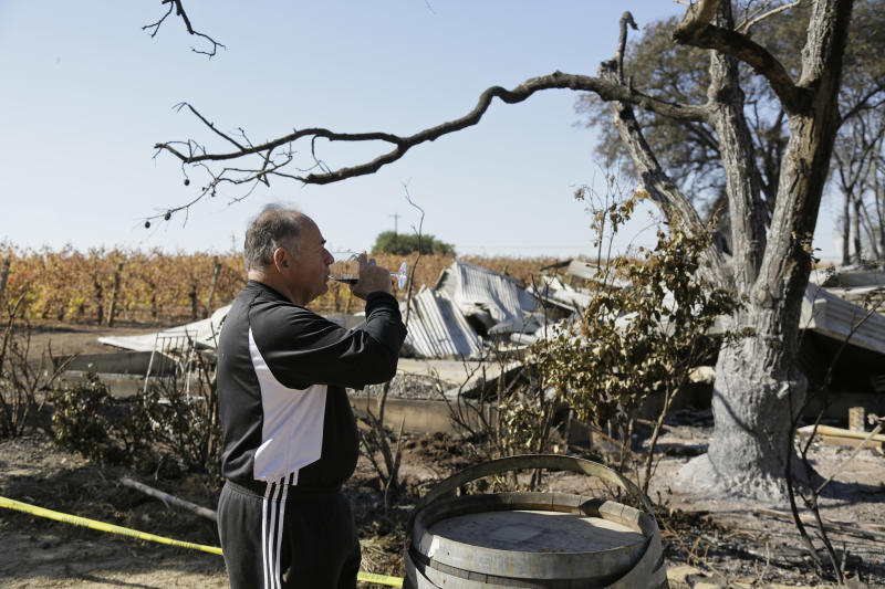 In this Wednesday, Nov. 6, 2019 photo, Izzy Lewkosky, of Kansas City, Kan., tastes a glass of Cabernet Sauvignon while looking out at the wildfire incinerated Soda Rock Winery in Healdsburg, Calif. Despite a late October blaze that raged through one of the world's best-known wine-growing regions. forcing evacuations in two mid-sized towns, wine production in Sonoma County escaped largely unscathed. (AP Photo/Eric Risberg)