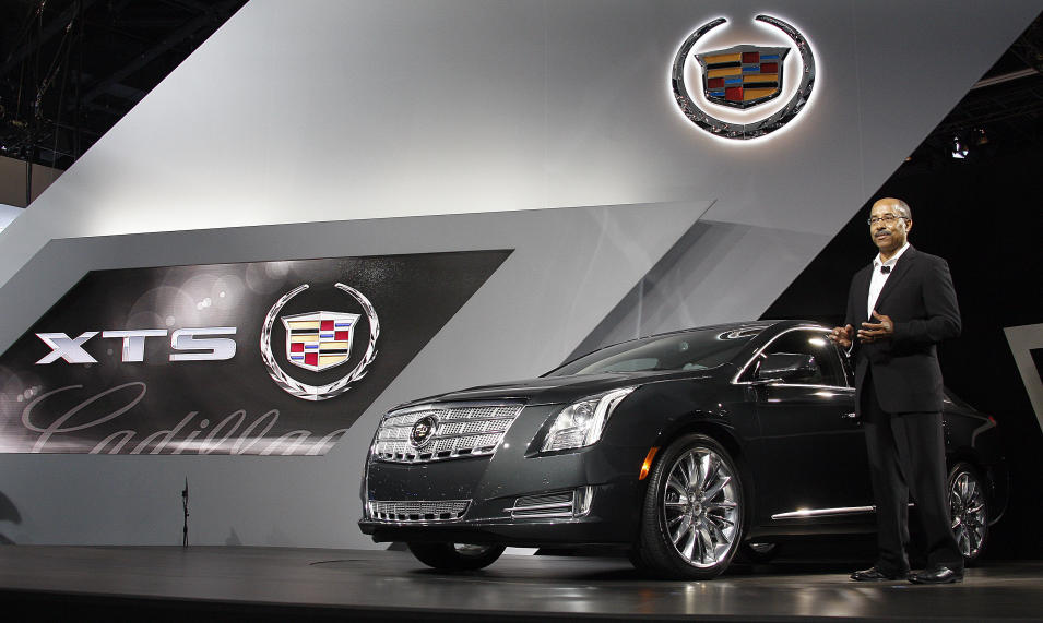 Ed Welburn, vice president of global design, stands with the Cadillac XTS at its debut at the Los Angeles Auto Show Wednesday, Nov. 16, 2011. General Motors Co.'s luxury brand unveils the replacement for its old land yachts, the DTS and STS. The company promises space and elegance with technology for a new generation of buyers. (AP Photo/Reed Saxon)