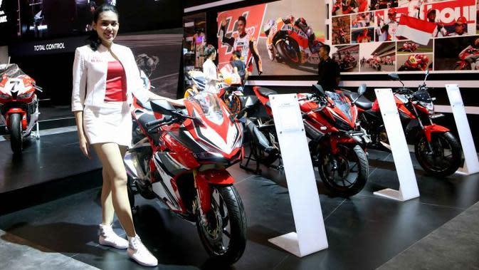 Seorang model berdiri disamping motor Honda CBR 250 RR.