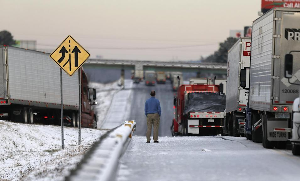 A man stands on the frozen roadway as he waits for traffic to clear along Interstate 75 Wednesday, Jan. 29, 2014, in Macon, Ga. A winter storm dumped snow and covered parts of the state with ice. Gov. Nathan Deal said early Wednesday that the National Guard was sending military Humvees onto Atlanta's snarled freeway system in an attempt to move stranded school buses and get food and water to people. (AP Photo/John Bazemore)