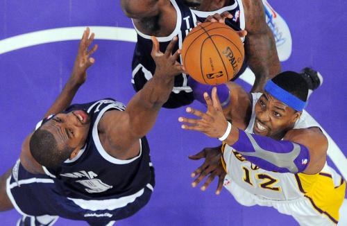 Oklahoma City Thunder power forward Serge Ibaka (9), of the Republic of Congo, and Los Angeles Lakers center Dwight Howard (12) reach for a rebound during the first half of their NBA basketball game, Sunday, Jan. 27, 2013, in Los Angeles. The Lakers won 105-96. (AP Photo/Reed Saxon)