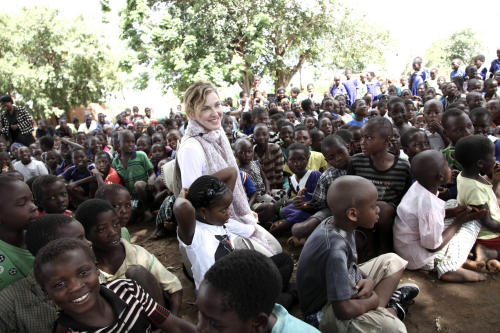 This image released by Liz Rosenberg Media shows singer Madonna visiting school children in Chorwe, Malawi on Wednesday, April 3, 2013. Madonna's foundation, Raising Malawi, has built ten schools in partnership with BuildOn which are currently educating over 4,000 students per year. (AP Photo/Liz Rosenberg Media)