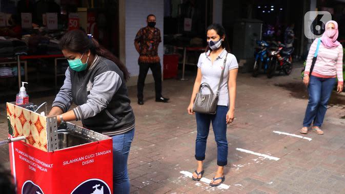 Pengunjung melakukan cuci tangan sebelum memasuki pertokoan di Pasar Baru (9/6/2020). Jelang pemberlakuan normal baru sejumlah toko di kawasan tersebut mewajibkan para pembeli untuk cuci tangan terlebih dahulu untuk menekan penyebaran Covid-19. (Liputan6.com/Angga Yuniar)