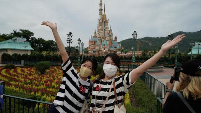 Pengunjung yang mengenakan masker berpose untuk foto di Disneyland Hong Kong pada Jumat (25/9/2020). Setelah dibuka dan tutup kembali, Disneyland Hong Kong dibuka kembali untuk wisatawan. (AP Photo/Kin Cheung)