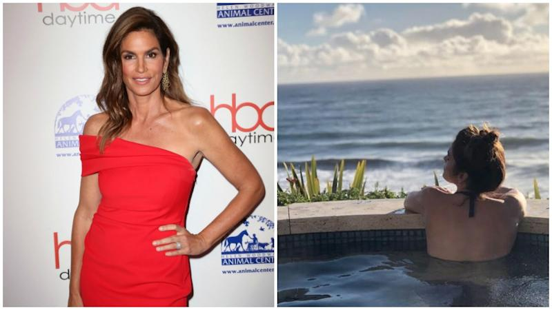 Cindy Crawford poses in a red dress and in a pool overlooking the water