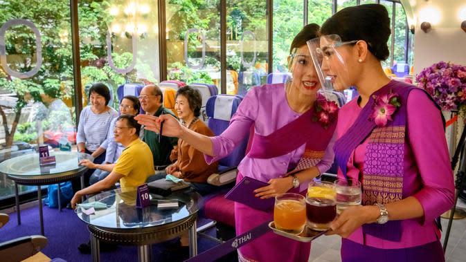 Pramugari mengenakan pelindung wajah saat melayani pelanggan di restoran pop-up bertema kabin pesawat di kantor pusat Thai Airways di Bangkok, 10 September 2020. Restoran pop-up ini awalnya hanya untuk sementara, tetapi antusias pengunjung membuat pihak maskapai berpikir ulang. (Mladen ANTONOV/AFP)