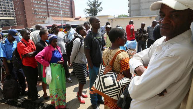 Orang-orang antre menarik uang kertas baru yang dikeluarkan Reserve Bank of Zimbabwe di Harare, 12 November 2019. Selama hampir satu dekade terakhir, masyarakat Zimbabwe menggunakan sejumlah mata uang negara lain bertransaksi pasca krisis ekonomi yang terjadi di Afrika. (AP/Tsvangirayi Mukwazhi)