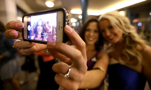 Miss America pageant alumni Miss South Dakota Calista Kirby, left, and Miss Rhode Island Kelsey Fournier take a photograph of themselves with a phone before the Miss America 2014 pageant, Sunday, Sept. 15, 2013, in Atlantic City, N.J. The former misses participated in last year's contest in Las Vegas. (AP Photo/Julio Cortez)