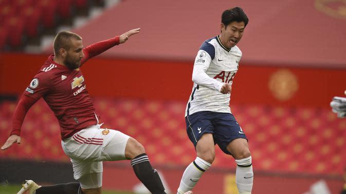 Bek kiri Manchester United (MU) Luke Shaw gagal mencegah pemain Tottenham Hotspur Son Heung-Min mencetak gol kedua ke gawang timnya pada pekan keempat Liga Inggris di Old Trafford, Minggu (4/10/2020). (Oli Scarff / Pool melalui AP)