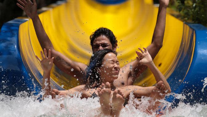 Pengunjung menggunakan pelampung meluncur di perosotan air terpanjang di dunia di Escape theme park di Teluk Bahang, Malaysia (25/9/2019). Pembangunan perosoton terpanjang di dunia ini dilakukan tanpa melakukan penebangan pohon. (AFP Photo/Sadiq Asyraf)