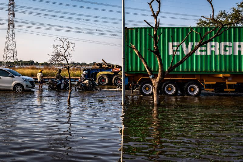 Vehicles move through a flooded road at an area affected by land subsidence and rising sea level, in Semarang