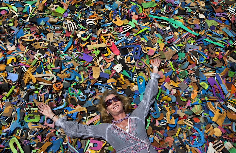 In this photo taken Monday, April 29, 2013, company owner and marine conservationist Julie Church poses for a photograph on a pile of pieces of discarded flip-flops used in a children's play area at the Ocean Sole flip-flop recycling company in Nairobi, Kenya. The company is cleaning the East African country's beaches of used, washed-up flip-flops and the dirty pieces of rubber that were once cruising the Indian Ocean's currents are now being turned into colorful handmade giraffes, elephants and other toy animals. (AP Photo/Ben Curtis)