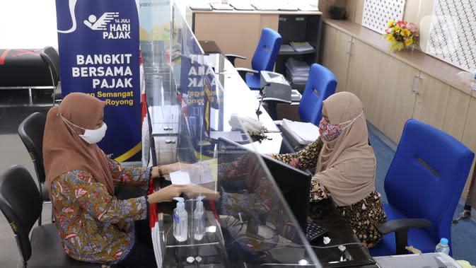 Petugas melayani warga melakukan pengurusan pajak di kantor Pajak Sudirman, Jakarta, Selasa (25/8/2020). Saat ini, pemerintah memberikan diskon sebesar 30 persen untuk mendorong pemulihan perekonomian nasional yang melemah akibat pandemi. (Liputan6.com/Angga Yuniar)