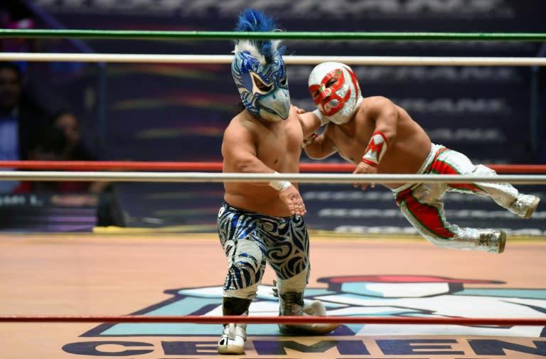 El mexicano Microman (rojo) vuela intentando derribar a su oponente durante una pelea de lucha libre mexicana en Ciudad de México el 7 de septiembre de 2018